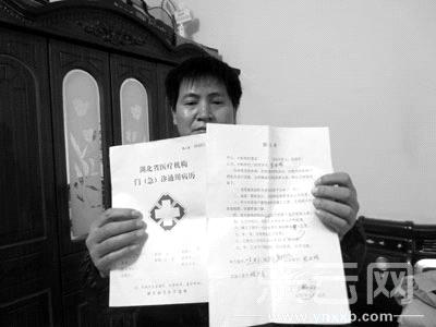 沈红霞丈夫向记者展示妻子的病历。