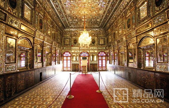 """墙壁上的花纹耐得住细看,工艺很细腻 玫瑰宫最华丽 格雷斯坦(Golestan)王宫位于德黑兰市中心,又称玫瑰宫,建于1865年至1867年间,为巴列维王室加冕以及接见外宾的场所。""""Golestan""""在波斯语的意思是""""有花的地方"""",这点无论从整个波斯风的庭园设计还是墙壁上那华丽的瓷砖上都可以得到印证。据说当时卡扎尔王朝的沙王在受邀游览欧洲各国后,对欧洲华丽的建筑风格大为赞赏,因此回国后下令兴建这座西式与波斯传统风格相结合的皇宫园林。特别订制的大理石王座被一群"""