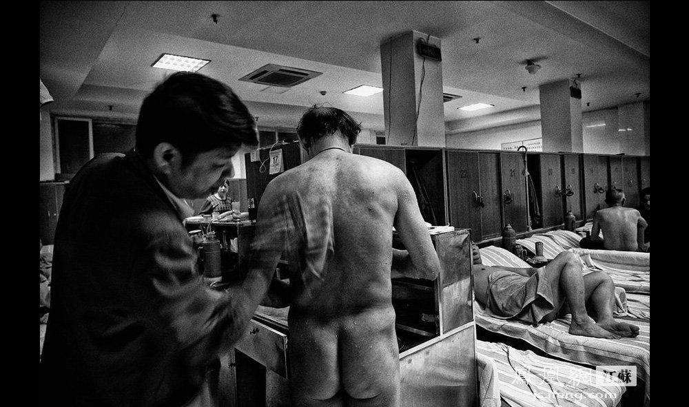 """浴室的牛岩在为提供客人""""出水""""服务——用热毛巾为顾客擦干身体。""""出水""""这个项目,目前只有传统的南京老澡堂才有。牛岩是淮安人,1996年来澡堂工作,因为技术好,待人谦和,当上了澡堂领班。(智德商旅--黄埔7号影像俱乐部/图 胥大伟/文)"""