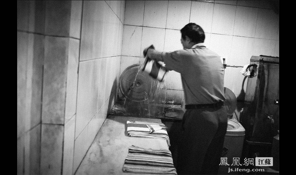 """郭师傅在手工拧毛巾。相比用机器压毛巾,手工拧毛巾是项技术活——在水温90度的热水里""""走一遭""""而不被烫伤是要有技巧的。郭师傅今年61岁,句容人,在澡堂里干了31年。他感叹,许多澡堂里的老手艺都失传了,像这手工拧毛巾如今也只有像他这样的老员工才会做。(智德商旅--黄埔7号影像俱乐部/图 胥大伟/文)"""