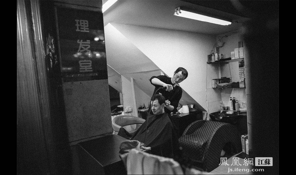 """一个浴客在理发。过去南京的老澡堂里不仅可以洗澡,还提供理发、餐饮、食品零售等其他服务。如今,人民浴室还保留着这些传统澡堂的""""标签""""。(智德商旅--黄埔7号影像俱乐部/图 胥大伟/文)"""