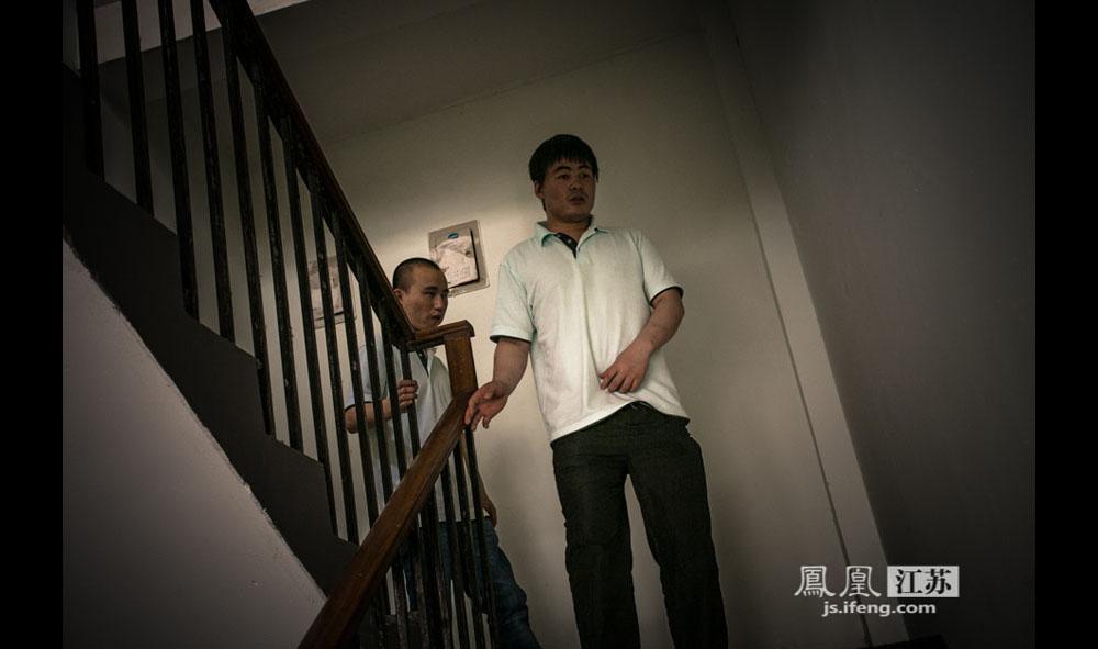 李明浩和同事出门下楼梯。这里的盲人医师平时很少出门,如果外出都是由一个稍微能感知光亮的技师带着完全看不见的医师,这样彼此有个照应。(彭铭/摄 胥大伟/文)