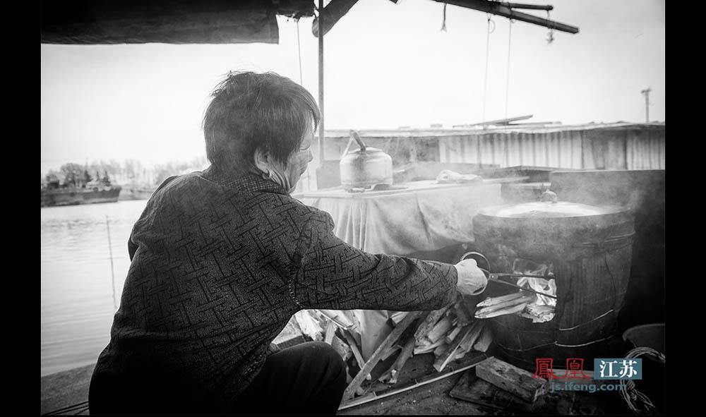 """因为嫌燃气灶贵,舍不得用,于光州烧菜做饭用的是""""缸缸灶"""",烧的柴火是她和老伴在岸上捡的。(林琨/摄 胥大伟/文)"""