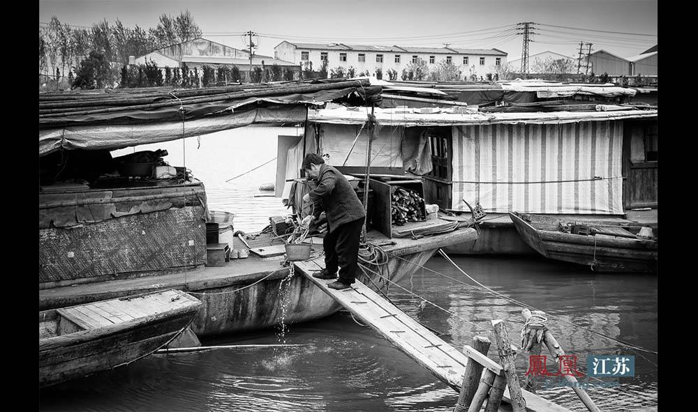 """于光州从秦淮河里打一桶水准备烧开了招待客人。当被问及""""水怎么不用明矾打一下"""",她有些面色局促的答道:""""一直就这样喝水,习惯了。""""(林琨/摄 胥大伟/文)"""