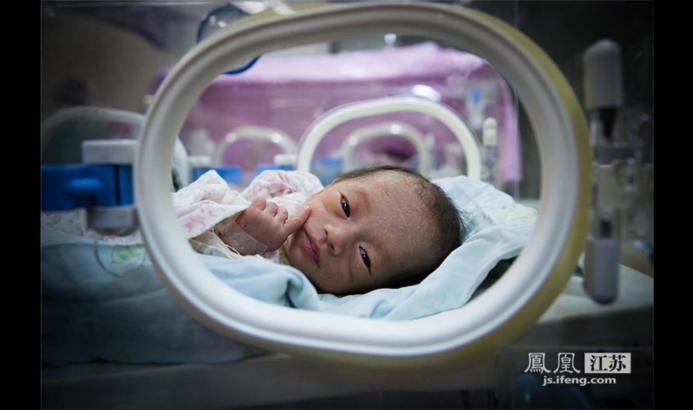 """在暖箱里的早产儿时常会睁开眼睛,但其实早产儿是完全看不到东西的,眼球的转动也是无意识的。当护士把手伸进暖箱,这些小家伙会下意识地抓住护士的手指,这也是一种""""条件反射""""。(林琨/摄 胥大伟/文)"""