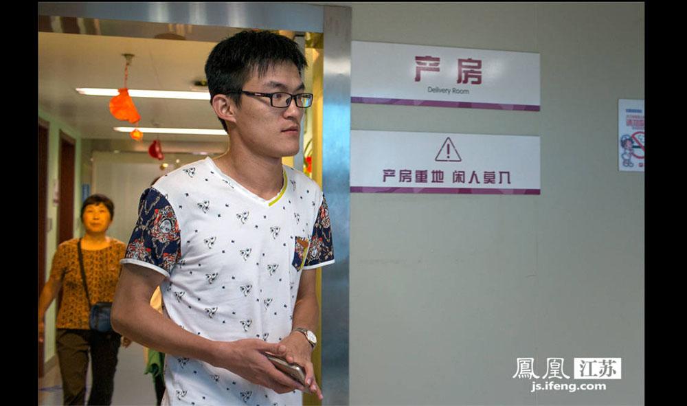 """杨磊为妻子送完午饭后从产房出来。6月16日上午9时,他妻子被推进产房待产。今年27岁的杨磊已经是第二次当爸爸了,他说这次感觉和第一次差不多,""""都有些紧张""""。杨磊是安徽滁州人,之所以来江苏省妇幼保健院生孩子是因为妻子是""""熊猫血"""", """"这里血源充足,各种血型都有,放心些。""""(薛晓红/摄 胥大伟/文)"""
