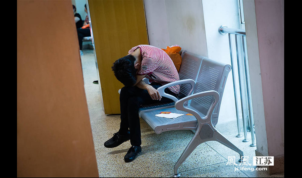一位年轻的父亲在产房外等待,因为疲惫,忍不住打了个盹。(林琨/摄 胥大伟/文)