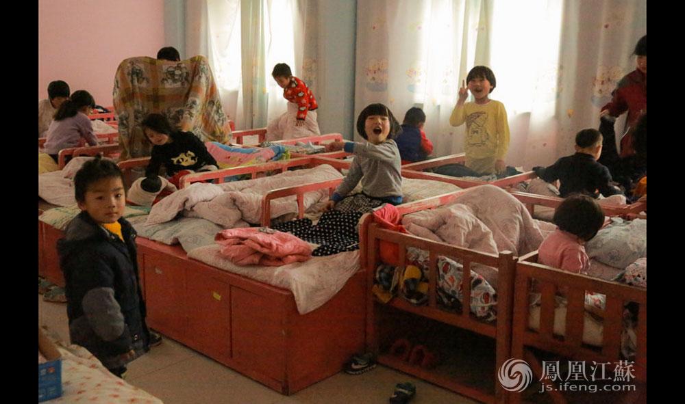 """宿舍分男女寝室,孩子普遍抵抗力较差,为此老师们总是把空调""""打得足足的""""。刚吃完饭的孩子精力充沛,常常很难入睡,老师往往得给他们讲上半个小时的故事才能安抚下来。在确保孩子们都睡着后,老师才会""""眯一会""""。朱园长说,中心一共有14位老师,年龄在25岁—40岁之间,都是清一色的""""娘子军""""。这里的听障儿童特教老师都必须要通过全国统一的轮训考试,有两三年的教学经验才能单独辅导孩子。(胥大伟 徐然/文 毛寿皓/图)"""