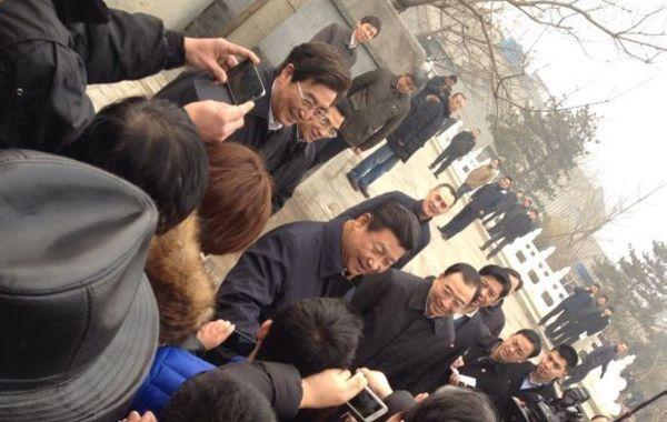 """2月25日,微博网友""""@国安低调哥""""发布微博""""习大大来南锣了!"""",并配有多张照片。照片上习近平出现在北京街头,与市民交流。北京市委书记郭金龙和市长王安顺陪同。25日北京持续雾霾天气,习近平现身北京街头引发热议,新京报官微转发该微博时称""""同呼吸,共命运!"""""""