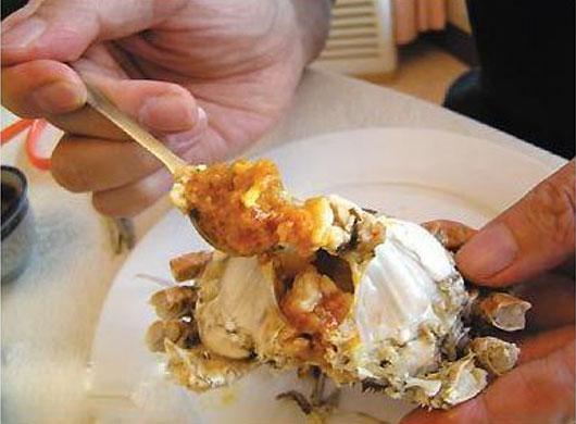 用小勺舀点醋淋在蟹身上,然后把蟹身的蟹黄蟹膏吃干净;