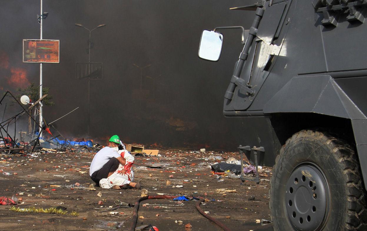 人民网8月14日讯 据CNN报道,埃及警方开始对前总统穆尔西支持者聚集的两处开罗营地进行清场,铲除帐篷,投放催泪弹,驱逐示威者。一处是开罗东部的Rabaa al-Adawiya清真寺,另一处是开罗西部的纳哈达广场。图为清场行动中,一名穆尔西支持者保护另一名成员。