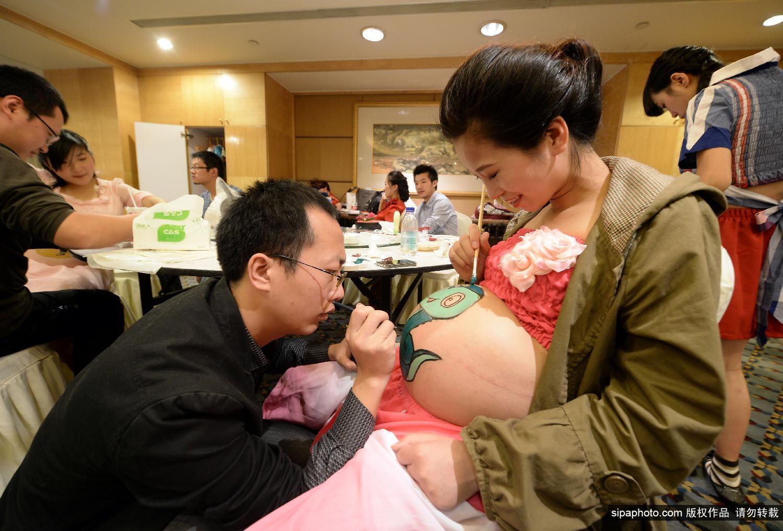 彩绘大赛.准妈妈们在自己挺起的肚子上绘画各种图案,代表着高清图片