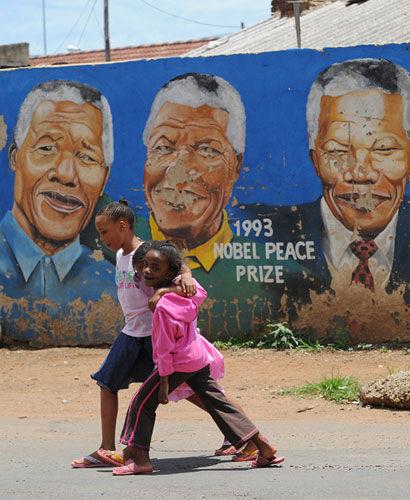 2012年12月10日,南非索维托,孩子们结伴走过曼德拉的壁画前。