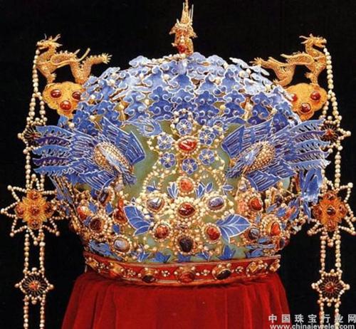头上戴的凤冠,以金属丝网为胎,上缀点翠凤凰,并镶嵌着珍珠等各类宝石