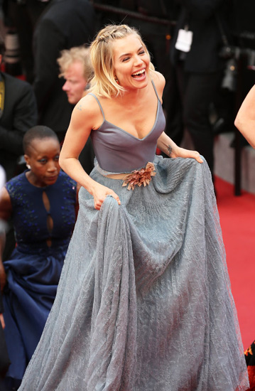 西耶娜-米勒穿吊带清凉亮相,性感爆乳自提裙摆大笑