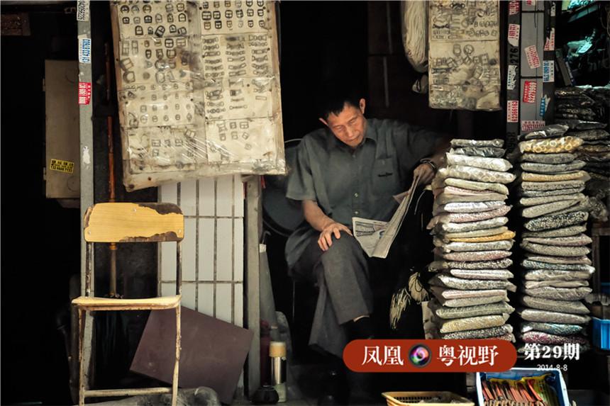 老人坐在皮革堆的缝隙中悠闲地看着报纸。