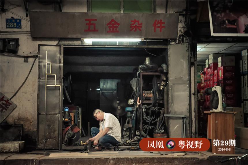 """在广州,凡是从事五金行业的人都会知道大德路,因为它的""""五金业""""已经存在了百年之久。图为:大德路一五金店主在店铺前修理零件。"""