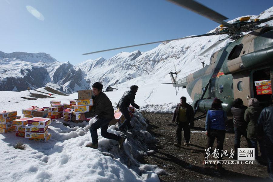 直升机空运物资到阿里雪灾区 当地女孩手机留念