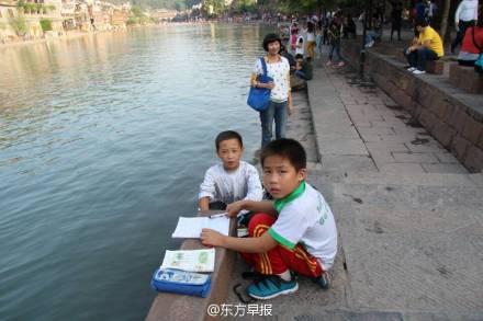 2名小学生沱江边写作业