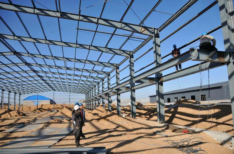企业创业园区一工厂厂房施工现场,建筑工人正在焊接厂房钢结构框架.