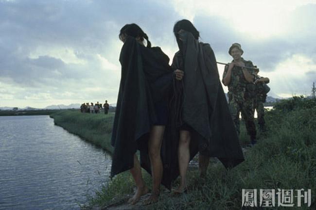 1979年5月6日,在广东深圳的边防前哨,突然聚集起近7万名来自广东各地的民众,形成数十条凶猛的洪流扑向边境线,边防军人束手无策,向天鸣枪示警也没用,几个哨位一下子被争先恐后非法越境的人流吞噬。图为驻港英军廓尔喀步兵旅的士兵押送逃港者前往遣返地。(图片来源:凤凰周刊)
