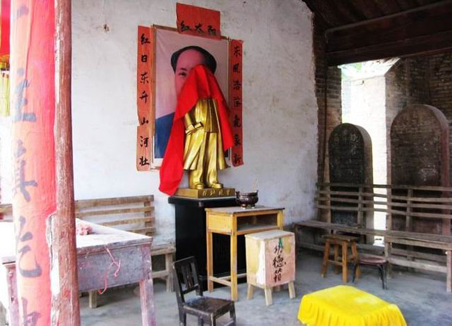 """1980年代,随着""""文革""""的结束,毛泽东走下了神坛;30年之后,毛泽东再次登上了神坛。佛教寺庙、道教宫观、民间神庙、土地爷、灶王爷的祭祀礼仪之中,随处可见人们祭奉的毛泽东像。有的地方,干脆就挂出了""""毛主席神庙""""的招牌。人们想升官、求发财、保平安、考大学、希望生活安定,乃至于整治腐败、以清官自勉,也要求祀于、祈福于毛泽东。图为河南修武一火神庙中供奉的毛泽东画像。(来源:凤凰网历史)"""