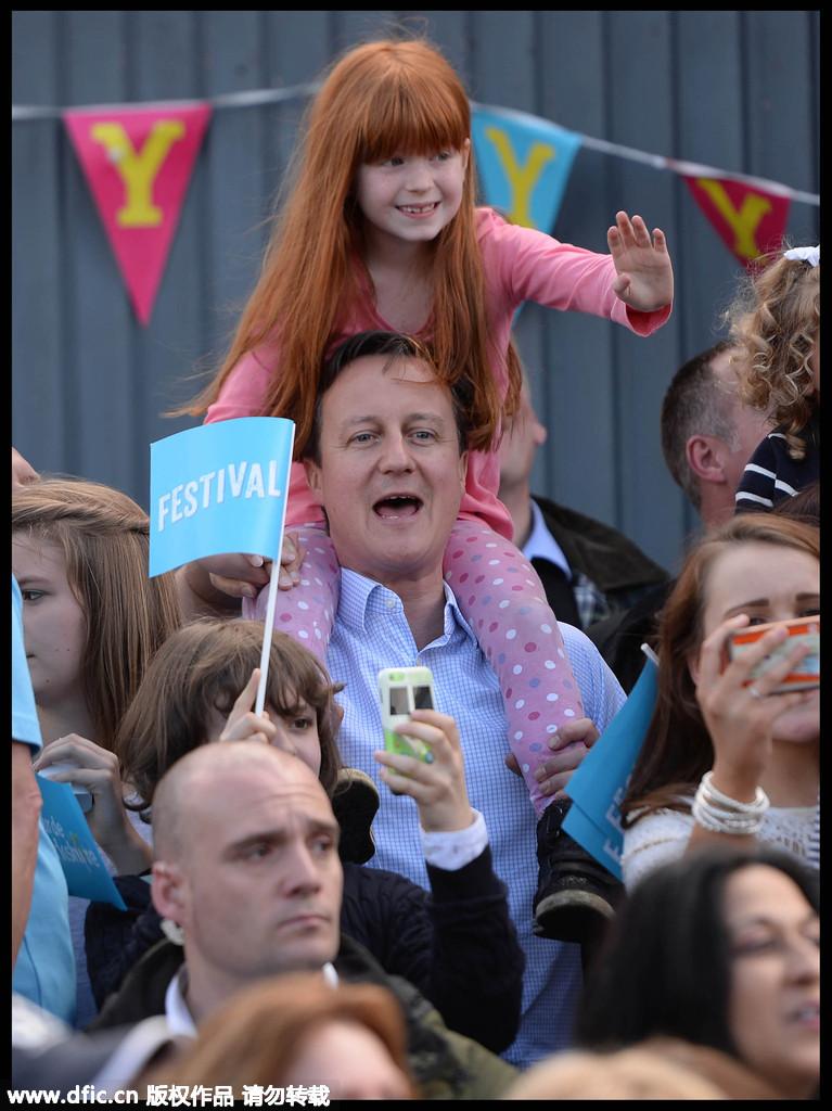 当地时间2015年5月3日,英国阿丁厄姆,英国首相卡梅伦观看环约克郡自行车比赛,为竞选积极造势,他将一名7岁女孩Amelie Bone扛在肩膀上秀亲民,这名小女孩获得了观看比赛的最佳视野,兴高采烈手舞足蹈。