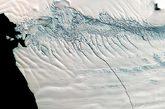 """近日,美国地球观测卫星""""Terra""""上搭载的光学感应器拍摄到南极派恩岛冰川出现30公里长的裂缝,一座巨型冰山正在形成。照片摄于去年11月。这条裂缝宽约80米,深约60米,长达30公里。据估计,不久之后一座面积约900平方公里的巨型冰山将会形成,并脱离冰川。"""