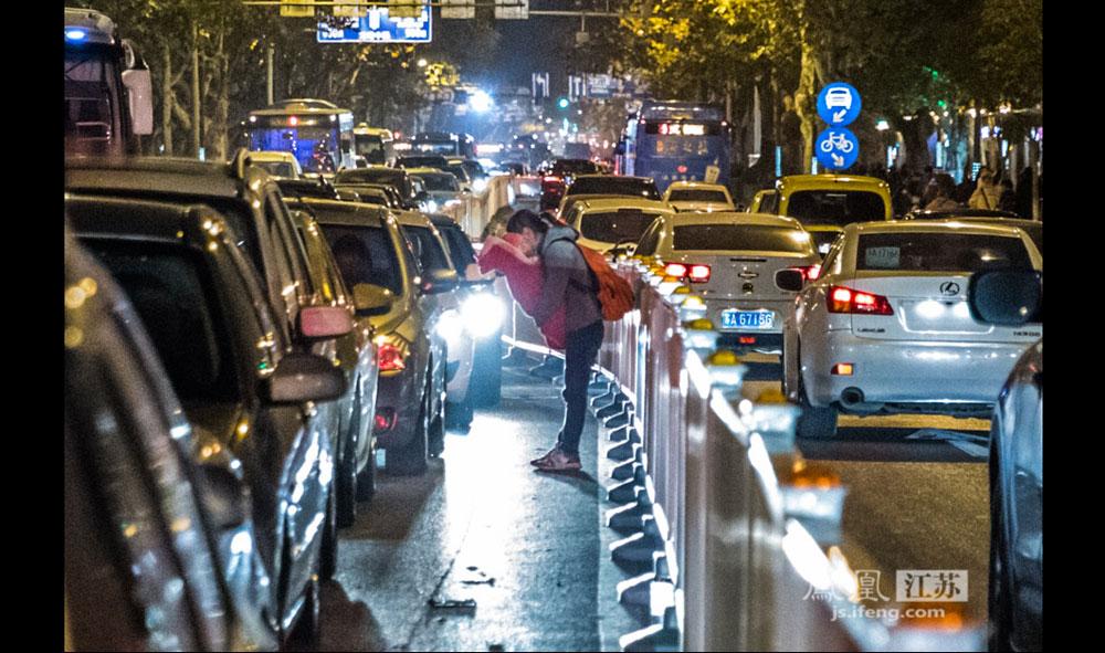 12月16日,南京闹市一条拥挤的马路上,一位来自甘肃的妇女抱着小孩向等红灯的司机讨钱。很多车主不耐烦地摆手让她走开。(彭铭/摄 孙子玉/文)