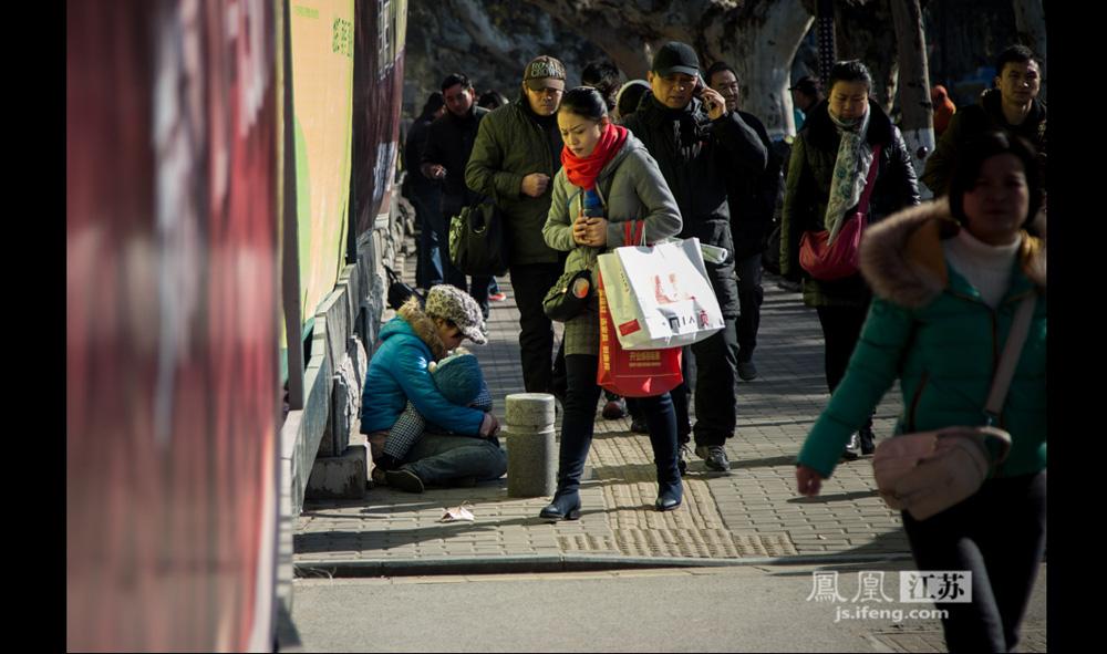 12月17日,南京某医院门口的人行道,一位30多岁来自甘肃的妇女抱着孩子坐在路边。她称丈夫残疾,去年家乡地震,尽管政府补助3万块钱,但他们还是修不起受损的房屋,只能出来乞讨。她家里还有一个7岁的孩子,由奶奶照顾。她自称刚来南京,之前在成都呆过两三个月。(彭铭/摄 孙子玉/文)