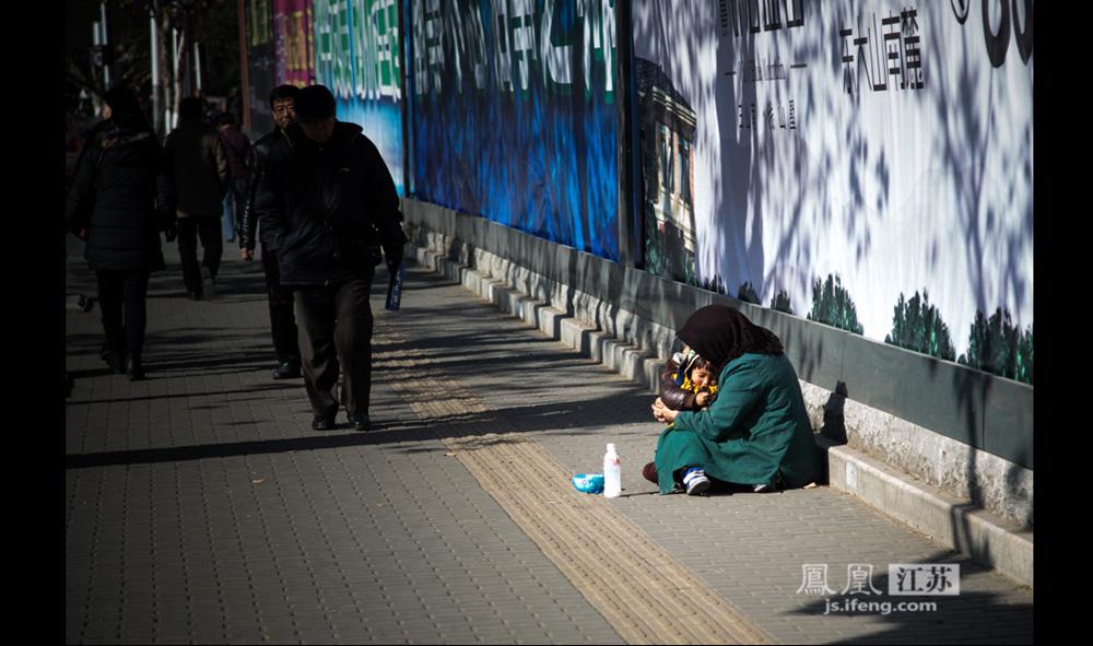 12月17日,南京某医院门口的人行道,来自甘肃的祖孙俩静静坐在路边。这位59岁的妇女亦称出来乞讨是因为家乡地震,没钱修房。(彭铭/摄 孙子玉/文)