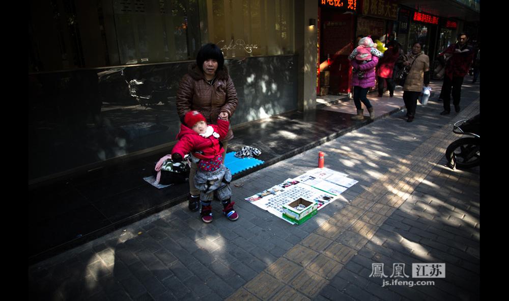 12月17日,南京儿童医院门口,一位40多岁来自安徽的妇女帮孩子学站立。妇女称孩子出生时确诊脑瘫,一年多前丈夫与自己离婚,她带着孩子来南京治病,十多万的医疗费用当地政府无法报销,只能带着孩子在街头乞讨。(彭铭/摄 孙子玉/文)