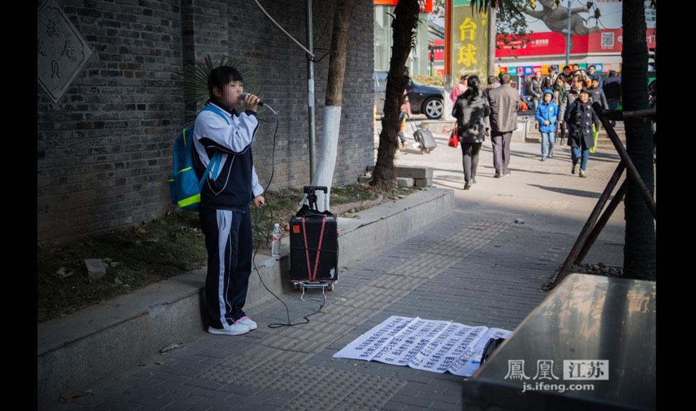 12月17日,南京某大学校门口,一位穿着校服的女子拉着音响举着麦克风唱歌。她面前的白纸上写着:妈妈因家庭经济困难而不得继续住院治疗疾病,并受病魔的折磨,面对为己求学还是为母亲治病的选择,我断然申请休学为治愈天底下伟大的母亲的疾病,奈何流落街头卖艺,在你垫底爱心帮助我母亲的病将会得到彻底的治愈,同时我能重返校园,我深深地渴望能得到大家的理解和帮助。(彭铭/摄 孙子玉/文)