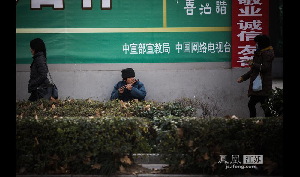 12月12日,南京紫峰大厦对面的一条马路边,一位来自山东年过六旬的男子吹笛卖艺。(彭铭/摄 孙子玉/文)