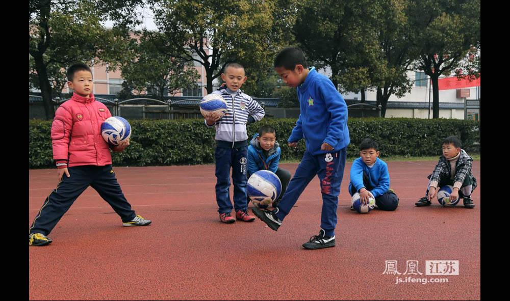 """二年级的金范羿(前)在队友们的围观下练习颠球。小家伙是队里的""""颠球王"""",最多时能颠500多个。金范羿的父亲说,因为儿子从小身体不好,于是从幼儿园开始就让他踢球锻炼身体,而他也逐渐地爱了这项运动。(缪宇欢 \ 图文)"""