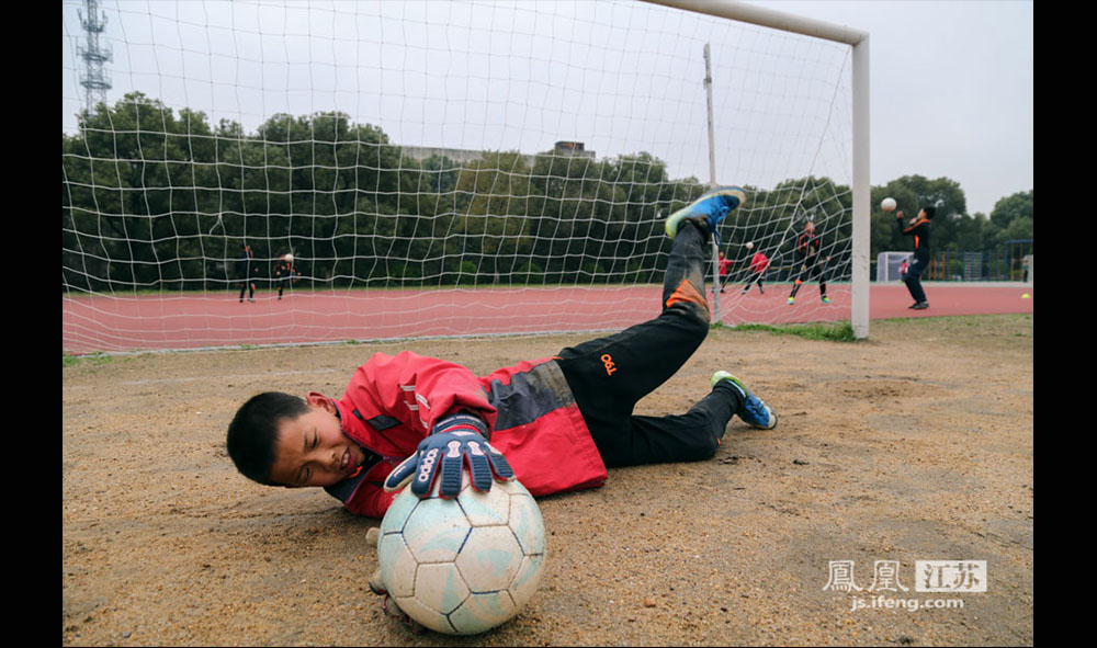 今年五年级的郑俊杰是球队的守门员,像这样的扑球动作他每天至少要重复四十次。一天下来,满身泥土。(缪宇欢 \ 图文)