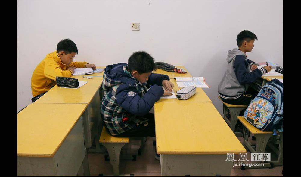 出于对孩子们的长远考虑,西张小学非常重视队员们的文化学习。蔡文浩(中)就曾因为没有按时完成作业而被暂停了足球训练。(缪宇欢 \ 图文)