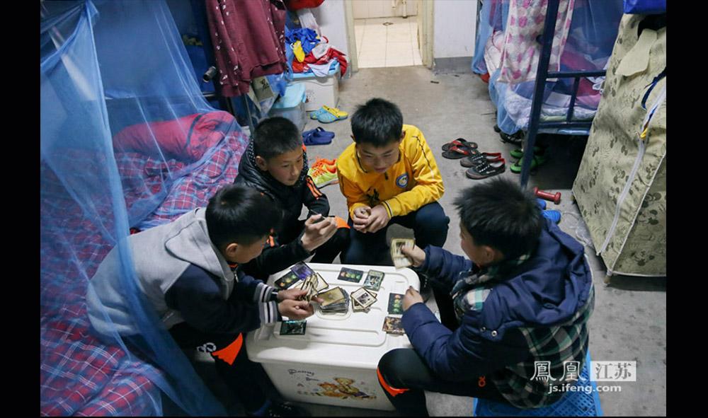 """西张小学的足球队员中,有4人家在外地,于是在校住宿,一周回家一次。爱玩是孩子们的天性。在宿舍里,玩""""三国杀""""纸牌游戏成了孩子们的一大消遣。(缪宇欢 \ 图文)"""
