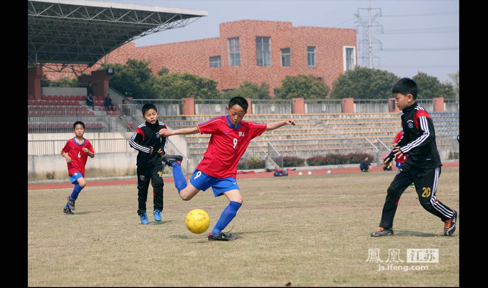 """比赛中,西张小学四年级的李毅(右二)积极拼抢、传球。他是队里的主力前锋,在场上无所畏惧,敢抢敢拼,人送外号""""小坦克"""",是教练看好的球员。(缪宇欢 \ 图文)"""