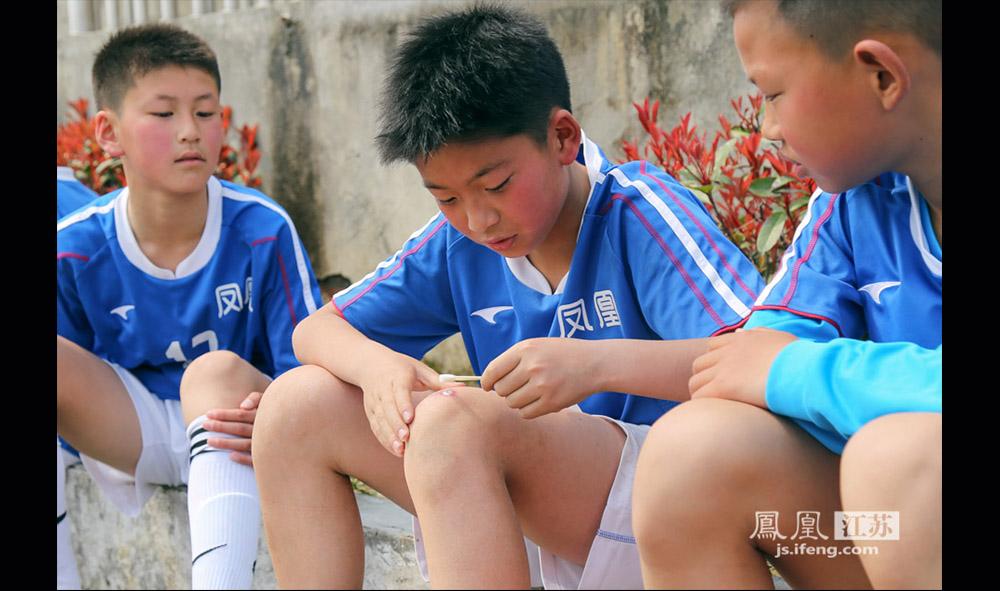 比赛激烈,受伤难免。西张小学的一位小队员在赛场边用碘酒擦拭伤口。(缪宇欢 \ 图文)