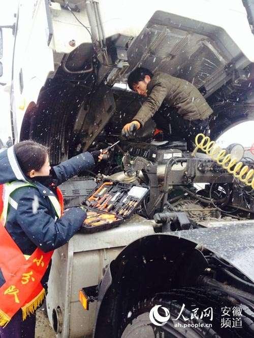 1月21日,九华山站收费员冒雪为司乘人员提供免费维修服务。