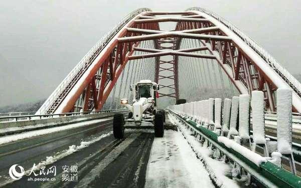 1月21日,平地机在铜汤高速太平湖大桥除雪。