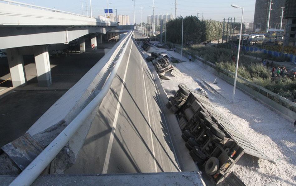 8月24日晨,哈尔滨市群力新区王家甸附近一跨江大桥数十米引桥发生整体塌落,4台货车掉落地面,有两具遇难者遗体停放现场。据消防部门消息,目前已造成3人死亡、5人受伤。图为事故现场。