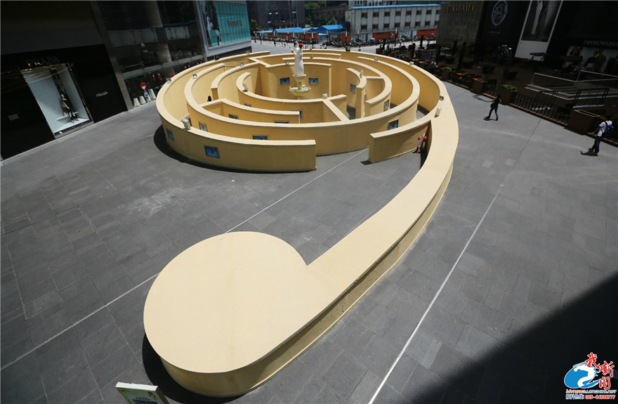这座户外迷宫装置位于南京新街口商圈,直径18米,木质结构,以迷