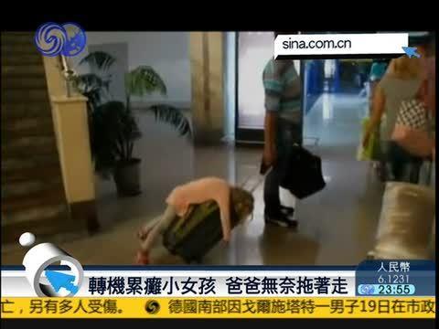 坐飞机累瘫小女孩 睡行李箱上被爸爸拖着走