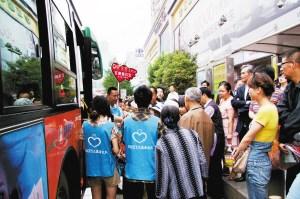 大学生志愿者在公交车站倡导文明乘公交。