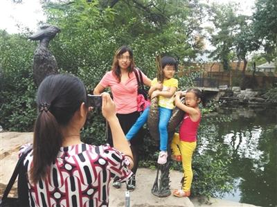 昨日,北京动物园,一家长让孩子坐在动物铜像上拍照.