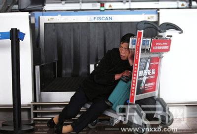 机场内,一名老人靠着行李车睡着了。