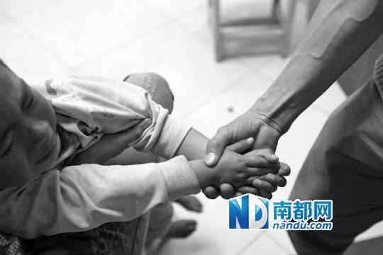 2月27日,广东阳江市人民医院,医生为阿B (化名)缝合耳朵伤口后,为了不让他乱动碰到伤口,父亲只好抓住他的双手。