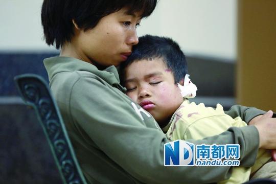 手术后,他在妈妈怀里睡着了。